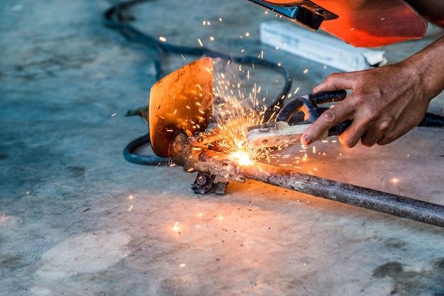 Der industriearbeiter, der schweißermaschine verwendet, schweißt ein spatenwerkzeug