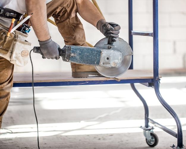 Der industriebauer arbeitet mit einem professionellen winkelschleifer, um ziegel zu schneiden und innenwände zu bauen. elektriker.