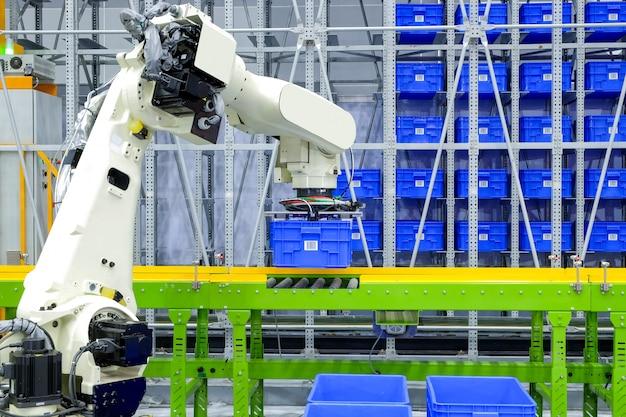 Der industrielle roboter, der blauen plastikkastenbehälter greift, setzte an förderer auf intelligentes fabriklager