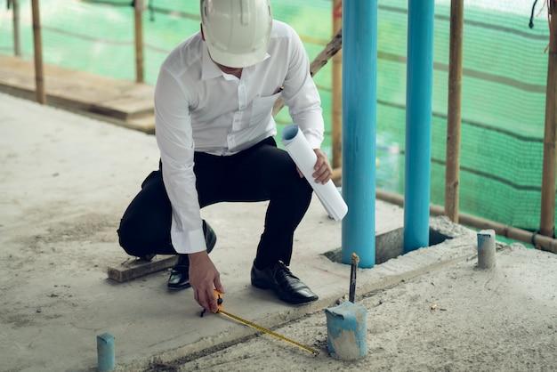 Der ingenieur, der den defekt auf der baustelle überprüft, misst den versatzabstand der hülse des boden-pvc-rohrs