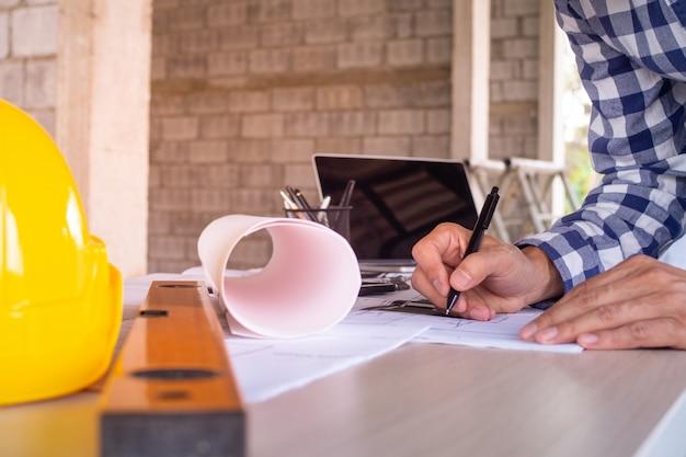 Der ingenieur entwirft, schreibt ein projekt, notiert es auf papier, um das haus zu überprüfen und zu reparieren, bevor er es an den kunden verkauft.