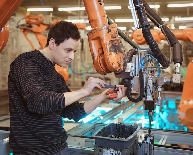 Der ingenieur führt die wartung des industrieroboters in einer fabrik durch