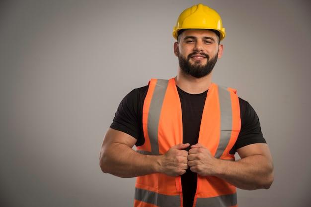 Der ingenieur in orangefarbener uniform und gelbem helm sieht zuversichtlich aus