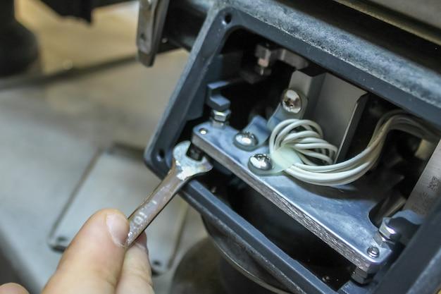 Der ingenieur passt die abmessungen kleiner lücken mit einem schraubenschlüssel in der wiegeausrüstung an. reparatur von wiegegeräten. branchenkonzept. spieleinstellung.
