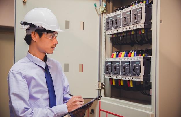 Der ingenieur prüft die spannung oder den strom mit einem voltmeter im bedienfeld des kraftwerks.