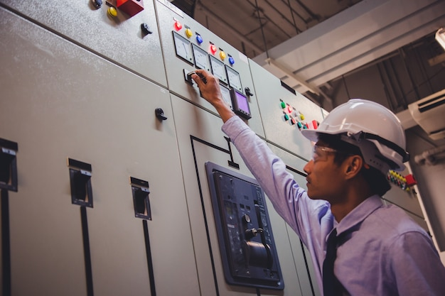 Der ingenieur prüft die spannung oder den strom mittels voltmeter in der schalttafel des kraftwerks.