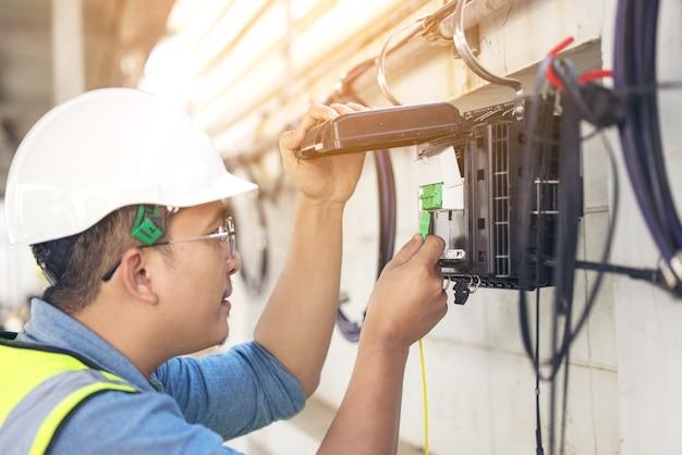 Der ingenieur repariert den anschluss der fasern an der splitterwanne aus der nähe von außen