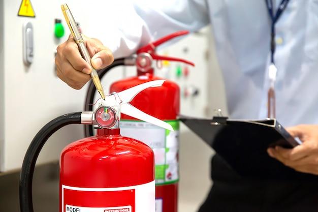 Der ingenieur überprüft und inspiziert einen feuerlöscher im feuerleitraum auf sicherheit und vorbeugung.