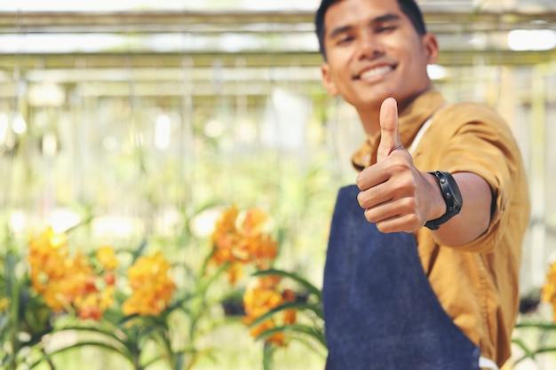 Der inhaber des orchid garden-geschäfts ist nach erhalt der investition mit seinem erfolg zufrieden.