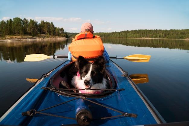 Der inhaber und der hund in einer schwimmweste, die in einem kajakboot schwimmt