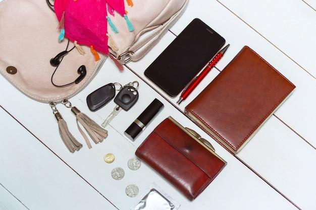 Der inhalt der damenhandtasche - portemonnaie, schlüssel, telefon, lippenstift, parfüm