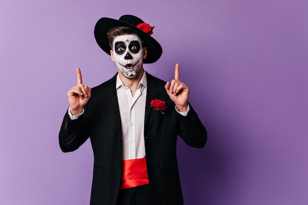 Der inspirierte typ mit mexikanischer gesichtskunst hatte eine großartige idee für die halloween-party.
