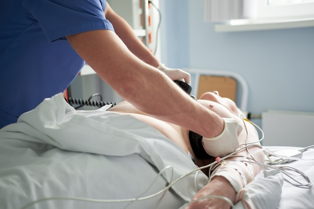 Der intensivarzt führt eine defibrillation bei einem kritischen patienten durch