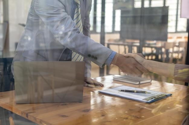 Der interviewer und der bewerber halten sich nach dem vorstellungsgespräch an den händen. das konzept der rekrutierung von mitarbeitern für die arbeit im unternehmen, vakante stellen.