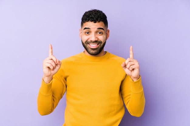 Der isolierte junge arabische mann gemischter rasse zeigt mit beiden vorderfingern an, dass ein leerzeichen angezeigt wird.