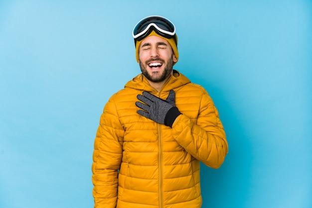 Der isolierte junge kaukasische skifahrer lacht laut und hält die hand auf der brust.