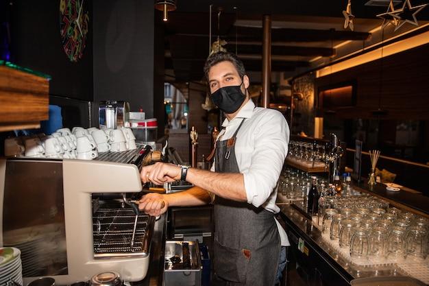 Der italienische barkeeper bereitet kaffee zu und schützt sich gleichzeitig vor dem coronavirus