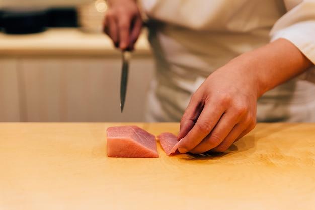 Der japanische omakase-koch schneidet mittelfetten roten thun (chutoro auf japanisch).