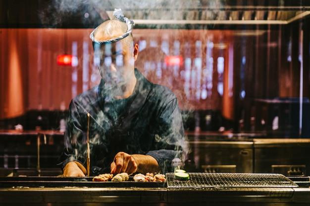 Der japanische yakitori-koch grillt hühnchen, das mit ingwer, knoblauch und sojasauce mariniert ist, mit viel rauch.