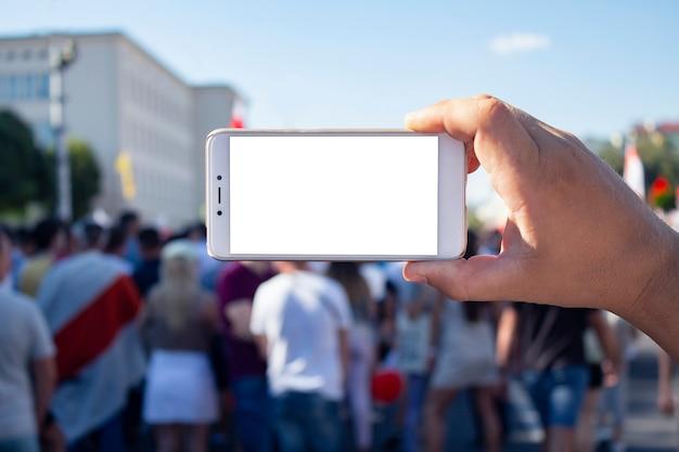 Der journalist hält ein smartphone in der hand und fotografiert protestierende aktivisten in belarus.