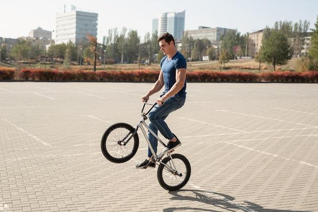 Der jugendliche bmx-fahrer führt tricks im skatepark durch