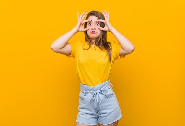 Der jugendliche der jungen frau, der ein gelbes hemd hält augen trägt, öffnete sich finden eine erfolgschance.