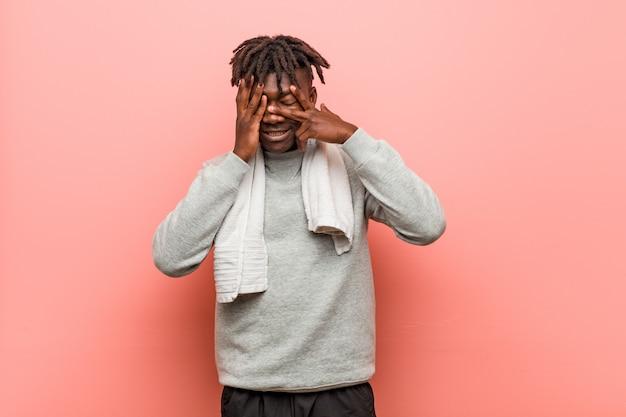 Der junge afrikanische schwarze mann der fitness blinzelt verängstigt und nervös durch die finger.