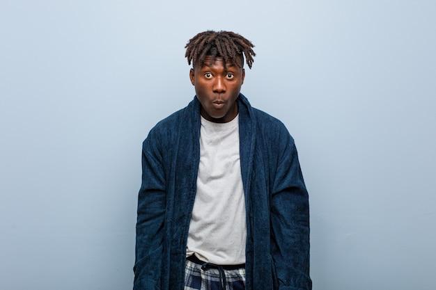Der junge afrikanische schwarze mann, der pyjama trägt, zuckt mit den schultern und die offenen augen, die verwirrt werden.
