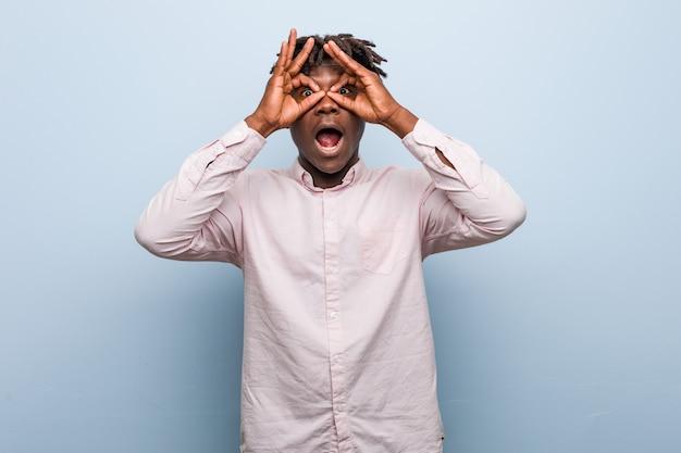 Der junge afrikanische schwarze mann des geschäfts, der okay zeigt, unterzeichnen vorbei augen