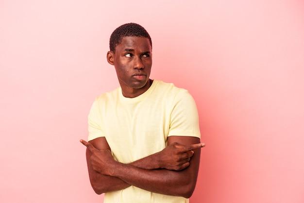 Der junge afroamerikaner, der auf rosafarbenem hintergrund isoliert ist, zeigt seitlich und versucht, zwischen zwei optionen zu wählen.
