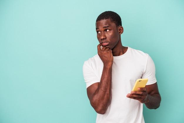 Der junge afroamerikaner, der ein mobiltelefon auf blauem hintergrund isoliert hält, entspannte sich beim nachdenken über etwas, das einen kopienraum betrachtet.