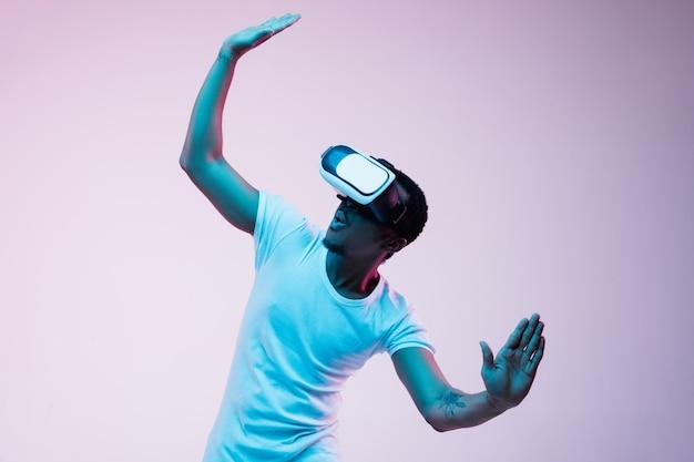 Der junge afroamerikaner spielt und verwendet vr-brille im neonlicht auf gradientenhintergrund