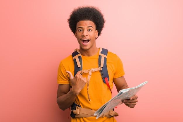 Der junge afroamerikanerforschermann, der eine karte überrascht hält, fühlt sich erfolgreich und wohlhabend