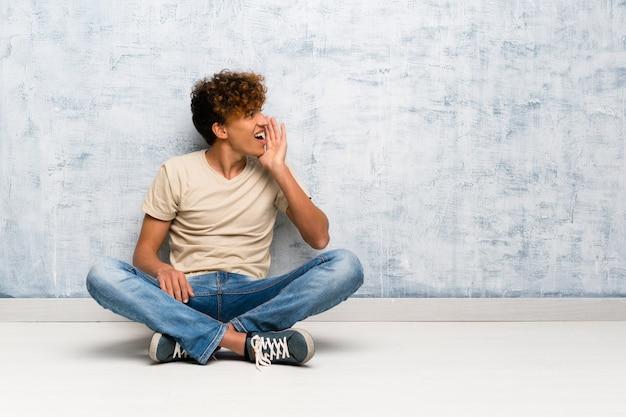 Der junge afroamerikanermann, der auf dem boden schreit mit dem breiten mund sitzt, öffnen sich zur seite