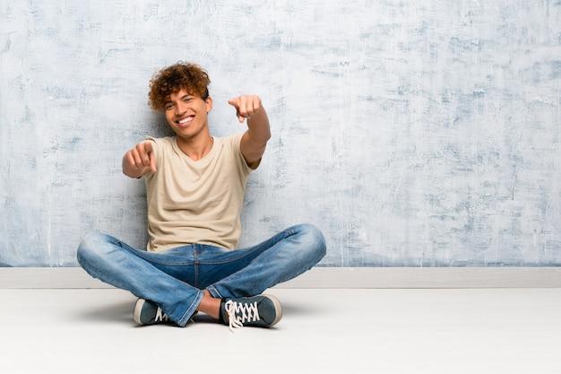 Der junge afroamerikanermann, der auf dem boden sitzt, zeigt finger auf sie beim lächeln