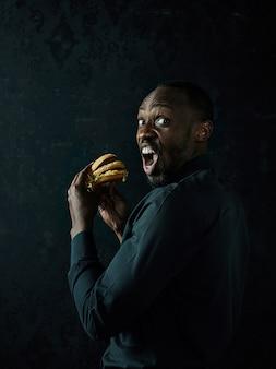 Der junge afroamerikanermann, der hamburger isst und weg auf schwarzem studio schaut