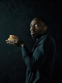 Der junge afroamerikanermann, der hamburger isst und weg auf schwarzem studiohintergrund schaut