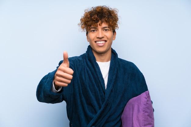 Der junge afroamerikanermann in den pyjamas gebend daumen up geste