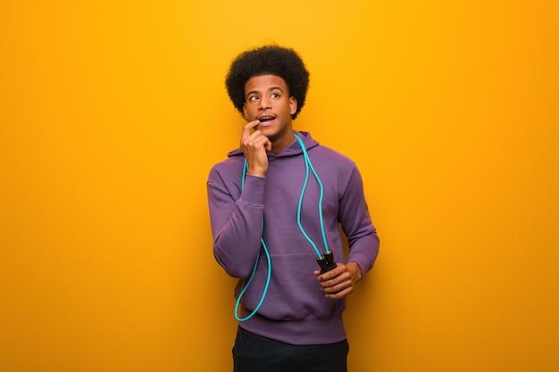 Der junge afroamerikanersportmann, der ein seilspringen hält, entspannte sich das denken an etwas, das einen kopienraum betrachtet