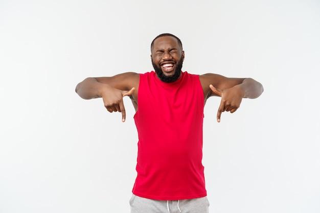 Der junge afroamerikanersportmann, der finger mit überrascht zeigt, fühlt sich erfolgreich und wohlhabend