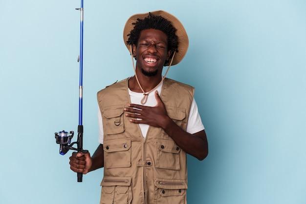 Der junge afroamerikanische fischer, der eine auf blauem hintergrund isolierte stange hält, lacht laut und hält die hand auf der brust.