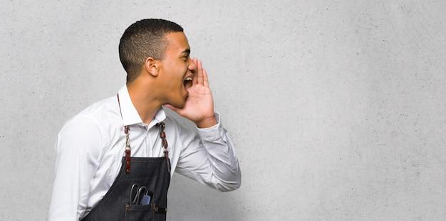 Der junge afroe-amerikanische friseurmann, der mit dem breiten mund schreit, öffnen sich zur seitenwand auf strukturierter wand