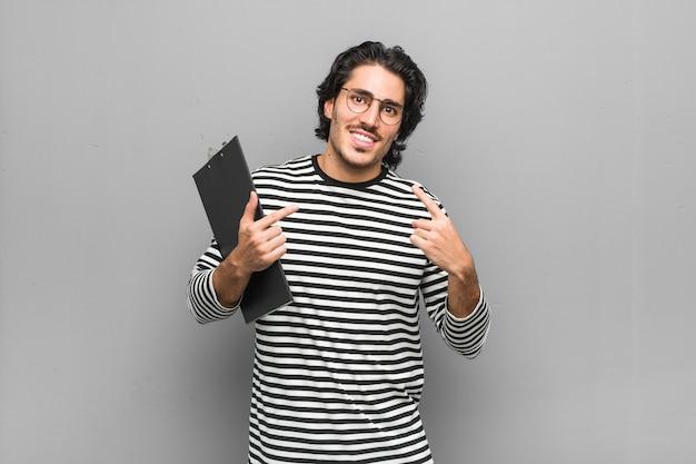 Der junge angestelltmann, der ein inventar hält, lächelt und zeigt finger auf mund.