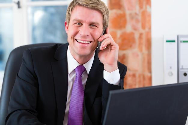 Der junge anwalt, der in seiner kanzlei arbeitet, auf dem schreibtisch sitzt und telefoniert, ist kunde oder mandant