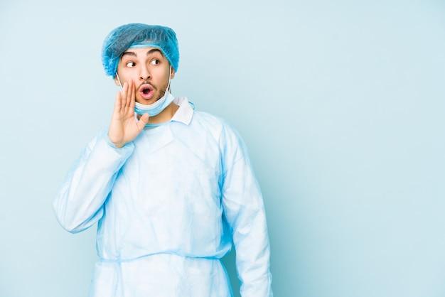 Der junge arabische chirurg, der gegen auf einer blauen wand isoliert ist, sagt eine geheime heiße bremsnachricht und schaut zur seite
