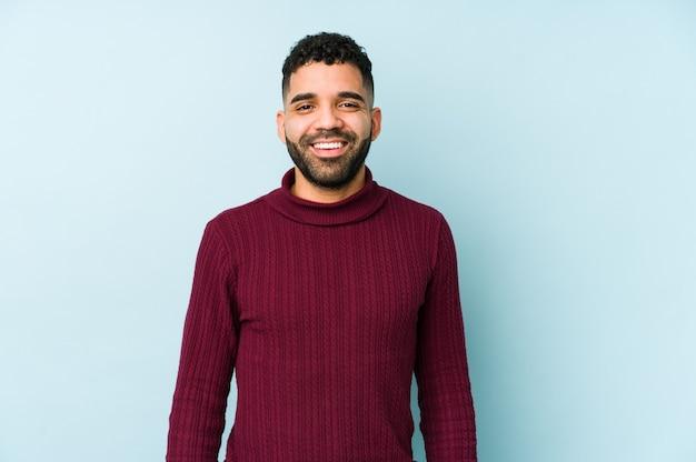 Der junge arabische mann der gemischten rasse isolierte glücklich, lächelnd und fröhlich.