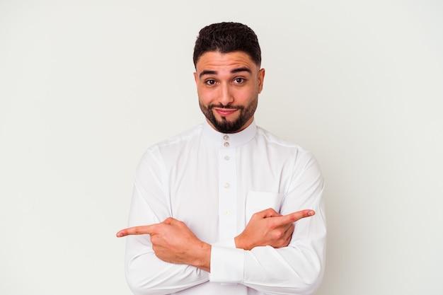 Der junge arabische mann, der typisch arabische kleidung trägt, die auf weißem hintergrund isoliert ist, zeigt seitlich, versucht, zwischen zwei optionen zu wählen.