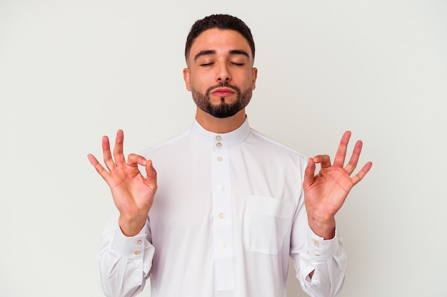 Der junge arabische mann, der typisch arabische kleidung trägt, isoliert auf weißem hintergrund, entspannt sich nach einem harten arbeitstag, sie macht yoga.