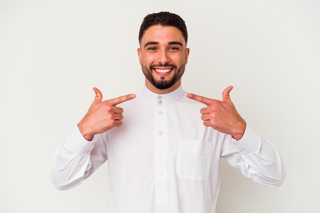 Der junge arabische mann, der typisch arabische kleidung trägt, isoliert auf weißem hintergrund, lächelt und zeigt mit den fingern auf den mund.