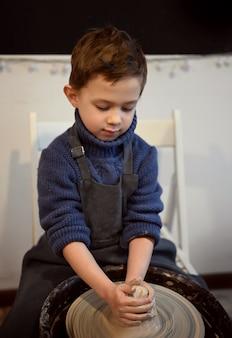 Der junge arbeitet an einer töpferscheibe. ein junge macht in einer töpferwerkstatt einen becher ton